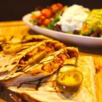 Tortilla arasında sotelenmiş,Tavuk parçaları,Renkli biberler,Acı jelapeno peynir,Salsa,Guacomole sos ve yoğurt