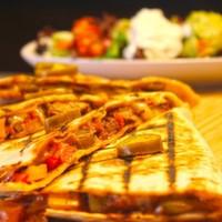Tortilla arasında sotelenmiş,Bonfile parçaları,Renkli biberler,Acı jelapeno peynir,Salsa,Guacomole sos ve yoğurt
