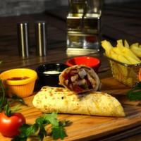 Tortilla ekmeği arasına ızgara köfte, iceberg, domates, turşu, soğan, eritilmiş kaşar peyniri, elma dilim patates